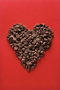 Heart made of chocolate chips on red background.