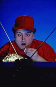 Guy in front of TV eating popcorn