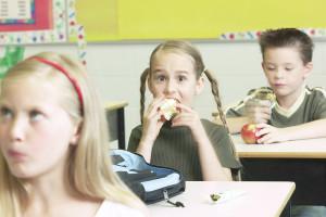 Girl in classroom eating apple