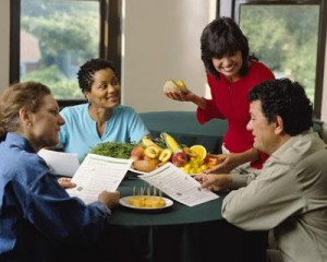 Lady standing with three others sitting around table with fresh produce