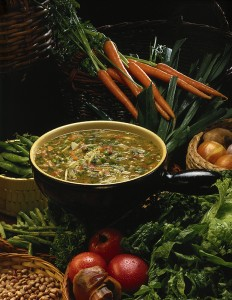 Soup in bowl with vegetables surrounding the bowl