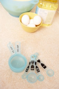 Measuring cups and spoons with eggs and oil