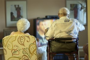 Older individuals sitting watching TV
