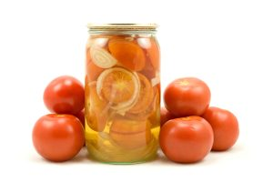 The clear glass jar of pickled tomatoes