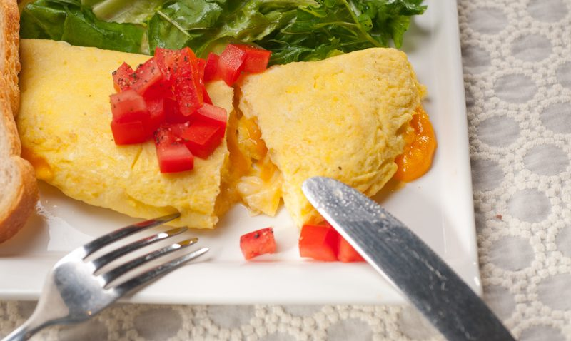 Egg omelet with tomatoes on a white plate
