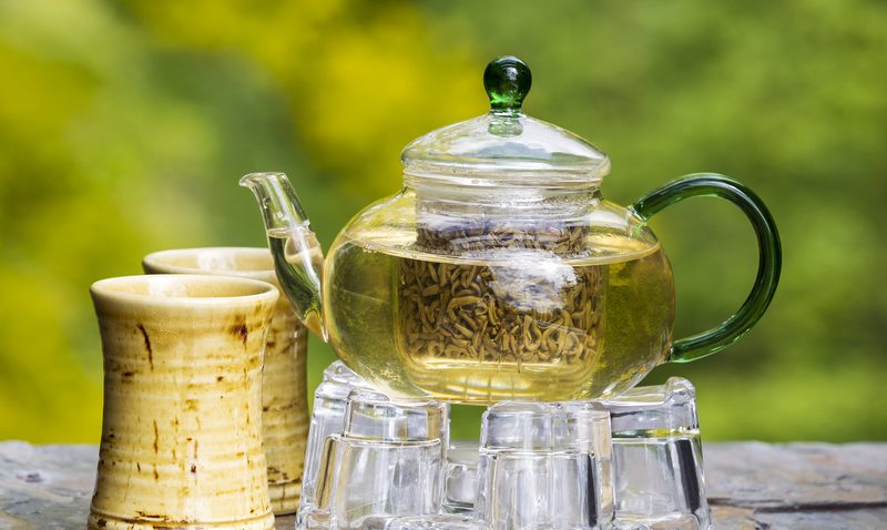 Brewing tea in clear pot with two cups