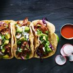 Three corn shell tacos with metal bowl of salsa and sliced radishes