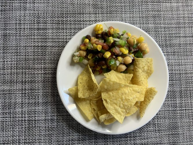 Recipe and corn tortilla chips on a white plate placed on a checkered tablecloth