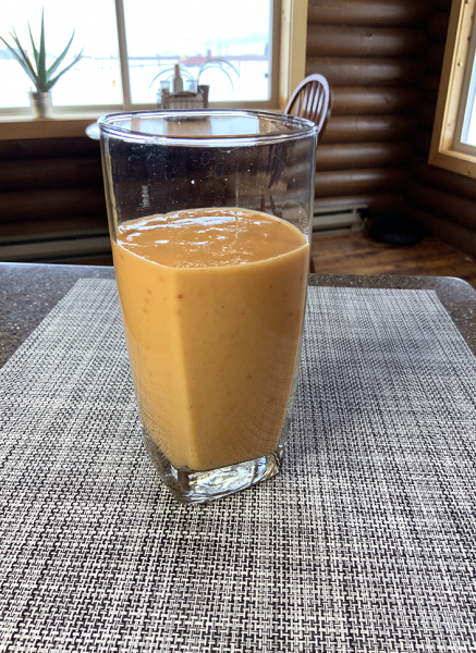 orange smoothie in clear glass on checkered placemat