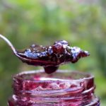 Fruit Jam on spoon coming out of jar