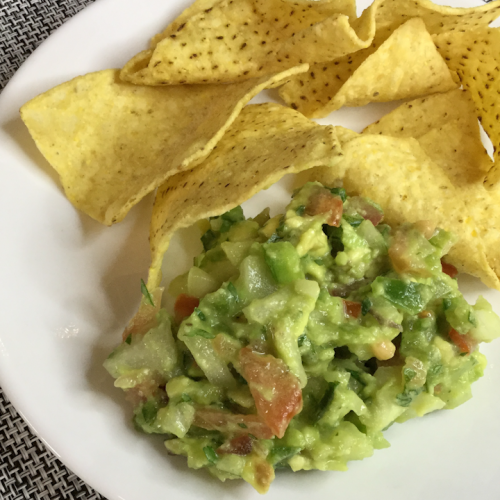 serving of guacamole with corn tortilla chips on white plate