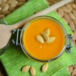 pumpkin soup with seeds on top. wooden spoon off to the side