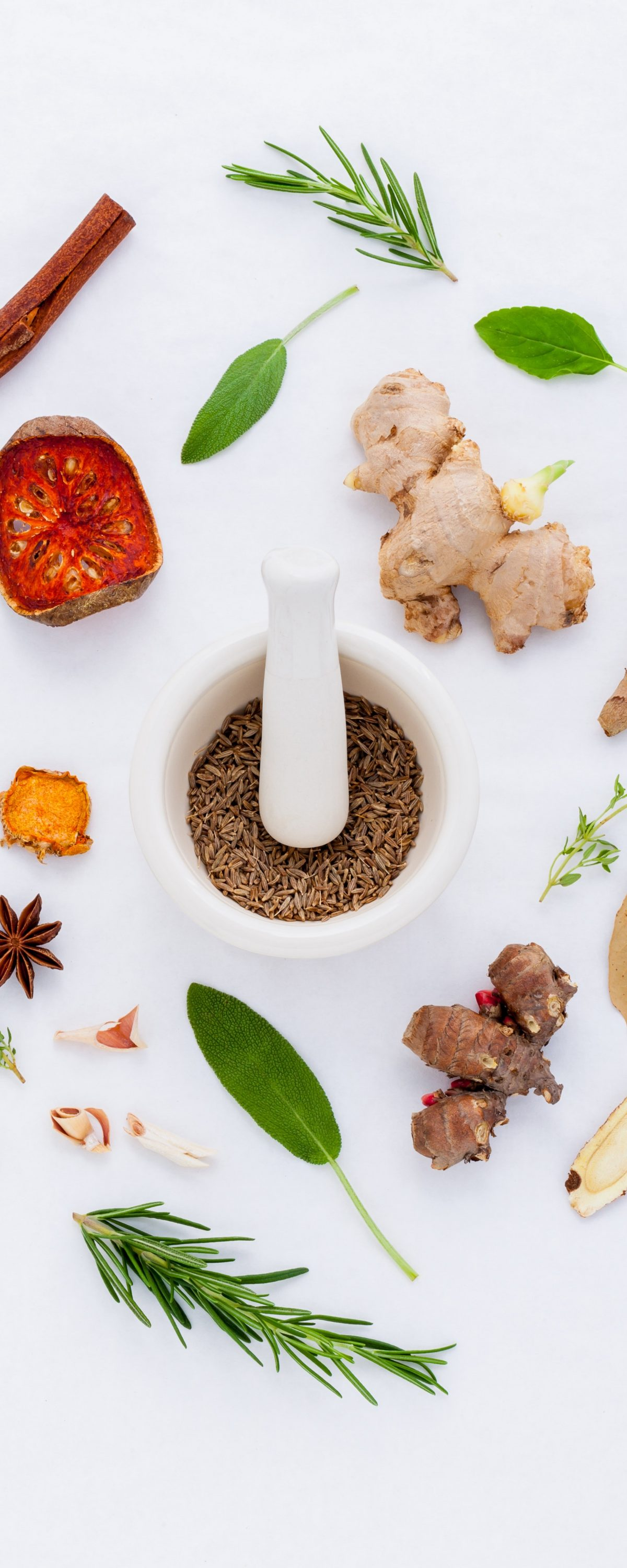 various whole spices arranged around mortar and pestle