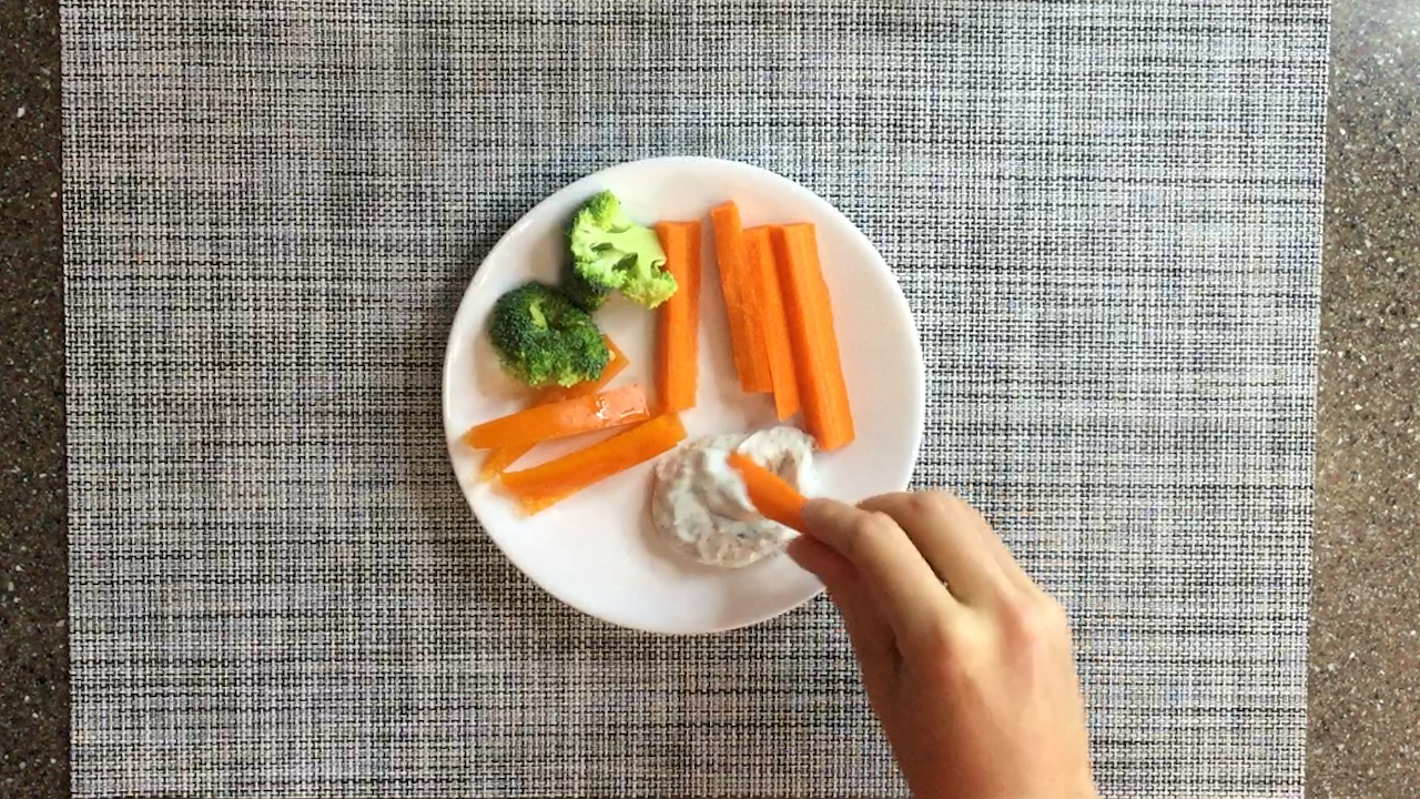 hand dipping carrot stick into dip