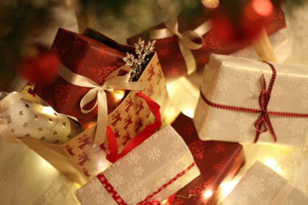 Wrapped Christmas gifts in red and white under a Christmas tree