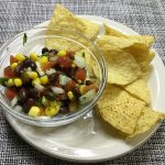salsa in small bowl with tortilla chips on plate