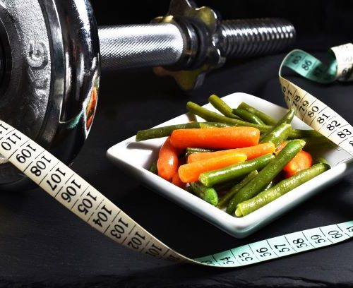 Bowl of vegetables with measuring tape and weights in background