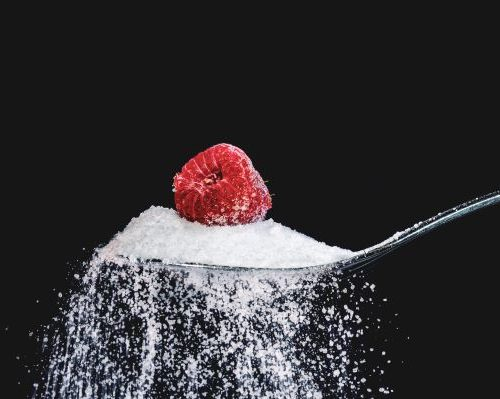 Spoon with sugar and one raspberry on top of sugar