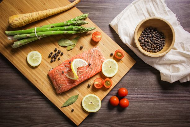 Raw salmon on cutting board with lemon slices asparagus, grape tomatoes, and peppercorns