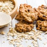 Oatmeal cookies next to a bowl of raw oats
