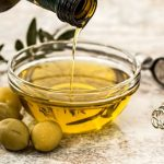 olive oil in glass bowl with olives on the side