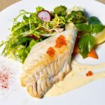 Halibut fillet on plate with salad