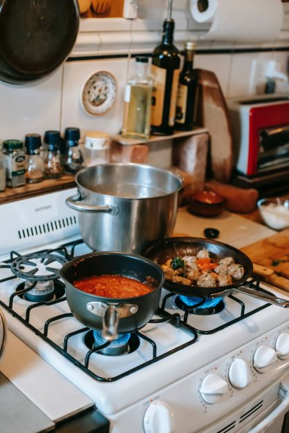 Image of three cooking pots on a gas stove with alcohol on the back shelf