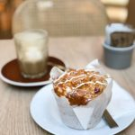 muffin on small plate with saucer and drink in background