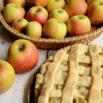apple pie with fresh apples off to the upper left hand corner in a basket